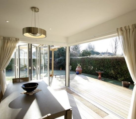 aluminium bifold doors in a corner configuration open to merge living room and external decking