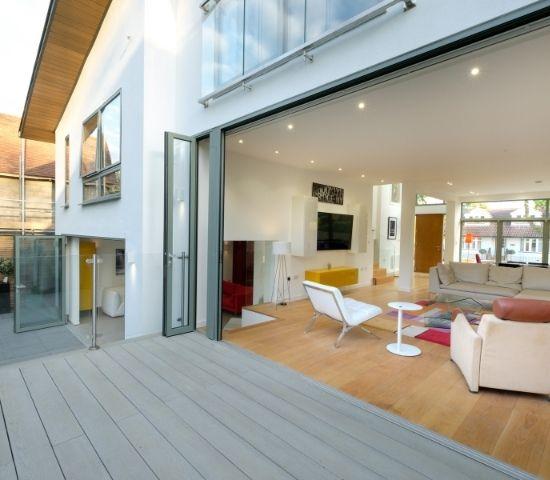 large aluminium bifold doors open to merge living room and external decking