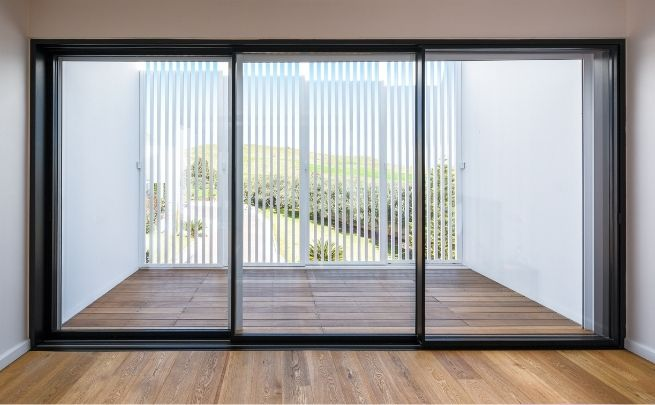 three track sliding glass door leading out to external balcony which also has wooden decking