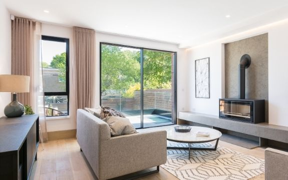neutral tone living room with a two pane sliding glass door leading to a balcony and a casement window