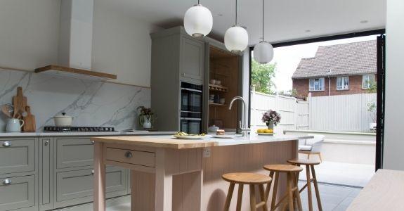 three pane aluminium bifold door bringing light into a pastel coloured kitchen extension