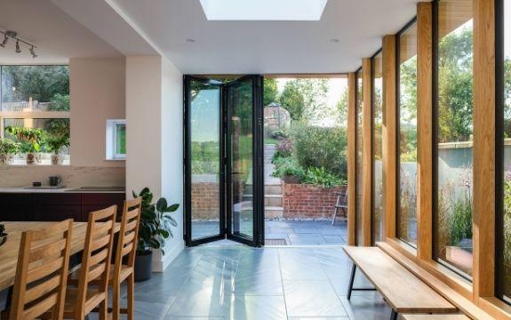 three pane black bifold door with tall fixed casement windows