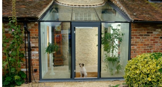 dog in open doorway of an aluminium framed glass door
