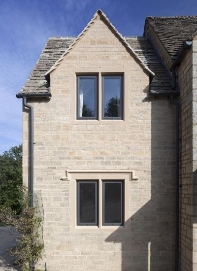 grey framed tilt and turn windows on a traditional architecture style home