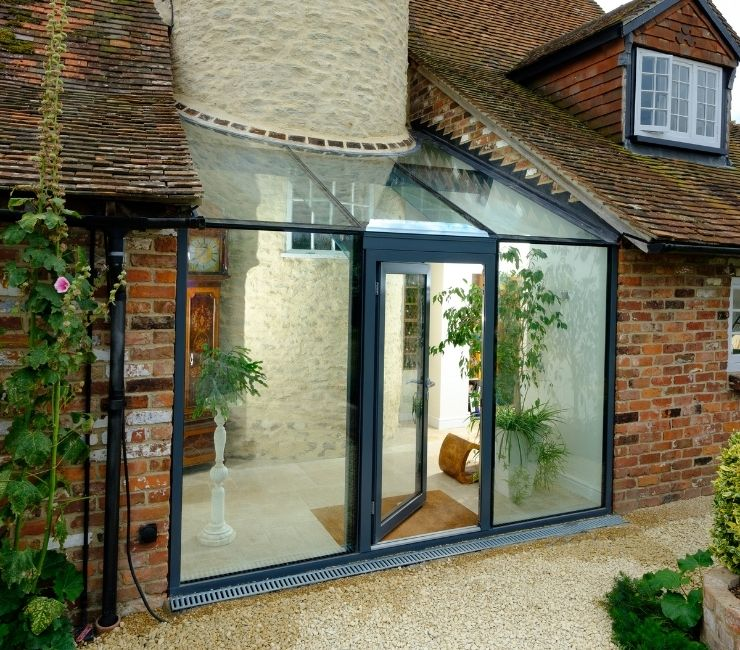 schuco aluminium casement door with fixed sidelights and an invio structural glass roof