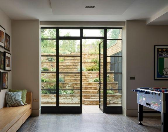 steel patio doors designed as a casement door with sidelights and dark steel framed glazing