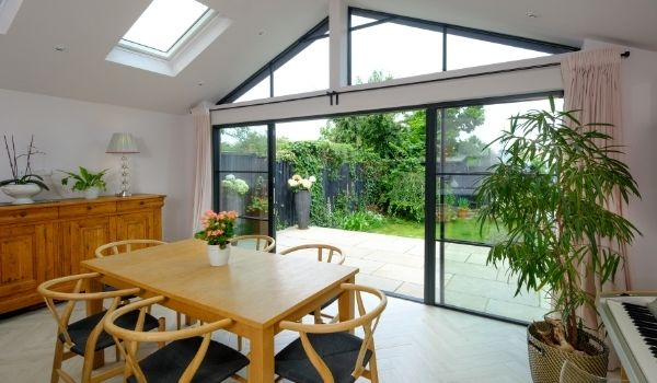aluminium slim sliding glass doors with glazing bar for an industrial style steel look aesthetic and house plants in a modern home extension - displaying elements of biophilic design