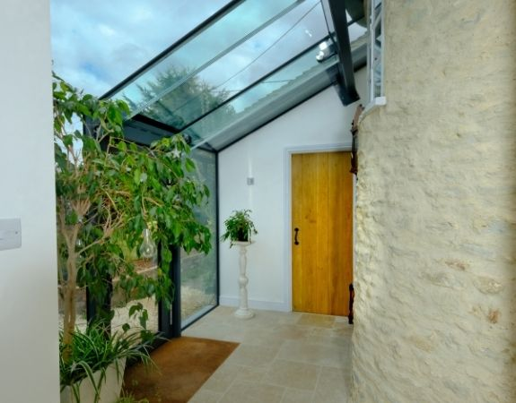 contemporary glass extension on an English cottage with invisio glass roof and large houseplants to create a strong connection to nature