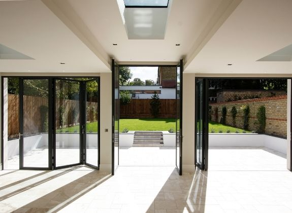 contemporary home extension with a tall casement door and slim bifolding patio doors either side