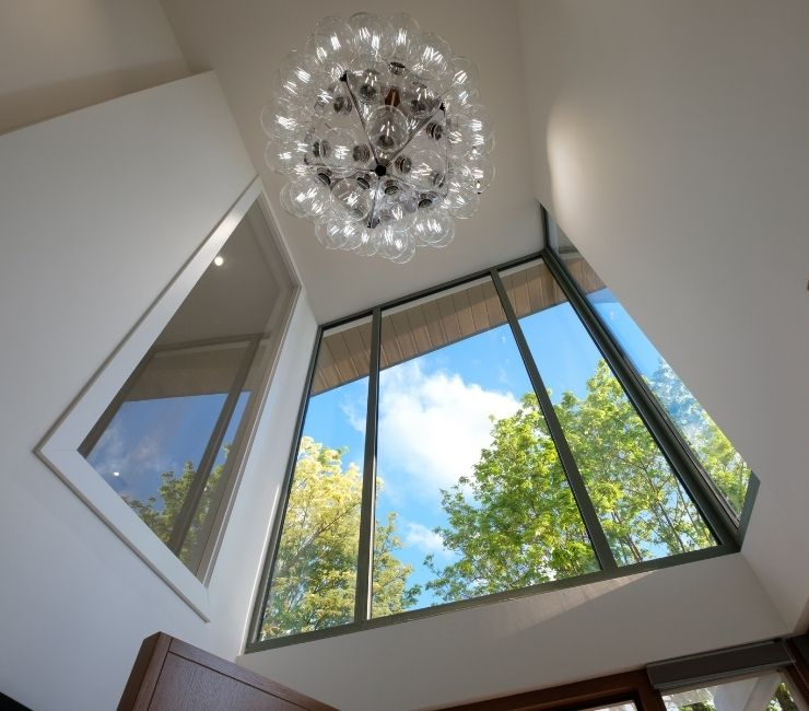 double height entrance way with fixed glazing and a unqiue light fixture to create a well lit inviting and modern home entrance