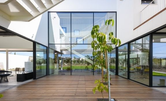 double height window design and large sliding glass doors that allows in vast amounts of natural light whilst providing clear views of the nature outdoors