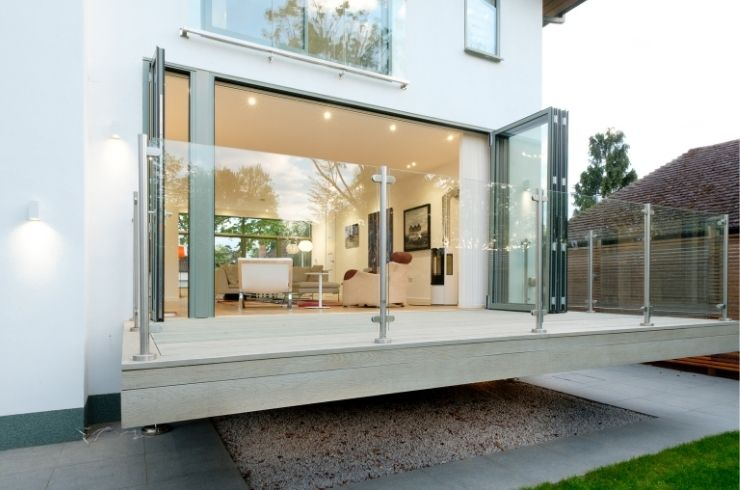 floating terrace with a glass balustrade and grey aluminium bifold door with a traffic door