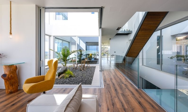 internal courtyard surrounded by slim sliding glass doors with aluminium frames and internal frameless glass balustrades