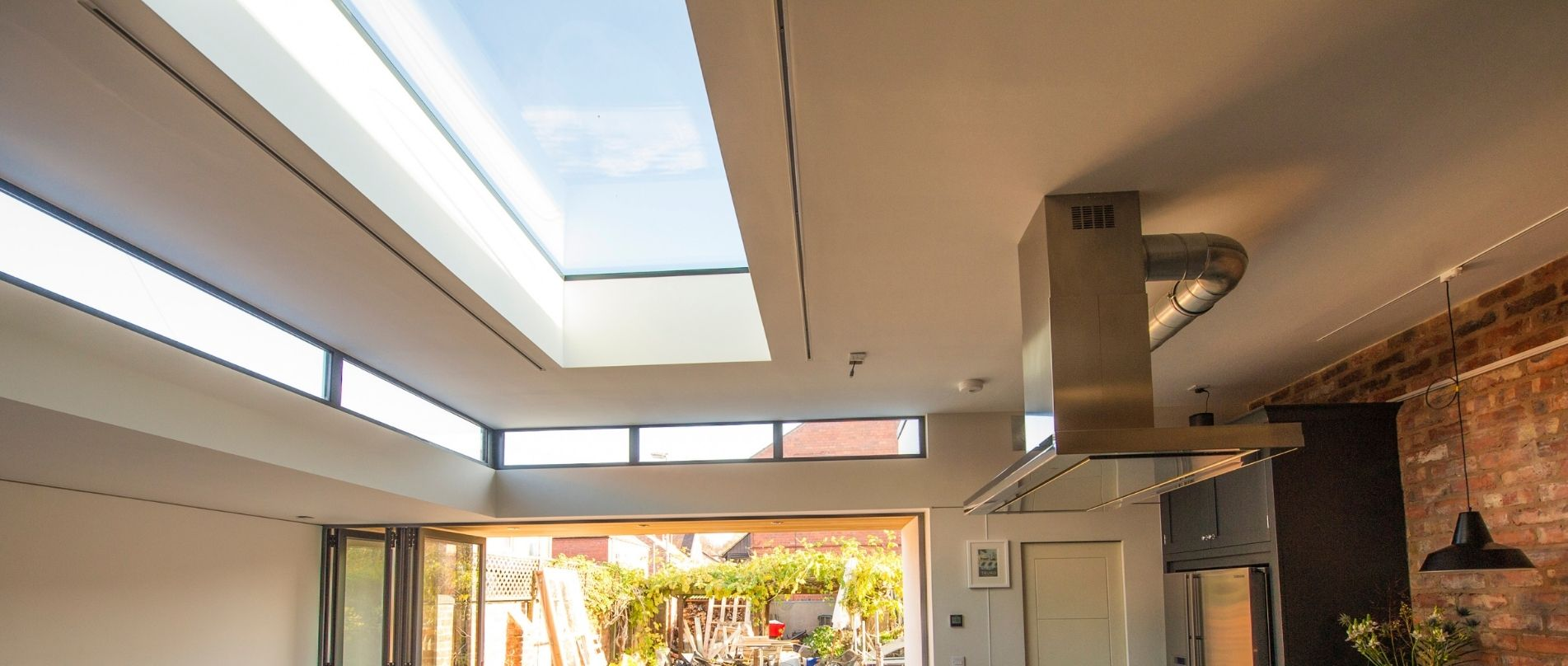 modern kitchen extension with a flat fixed aluminium rooflight and aluminium bifolding doors for maximum natural light