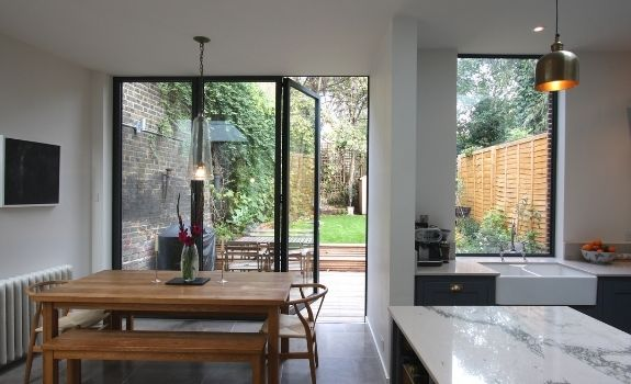 three pane aluminium bifold door and large fixed casement window with low maintenance coatings to create easy clean glass