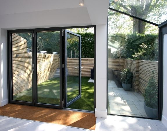 three pane aluminium bifold door and up and over structural glazing eaves window and roof glazing
