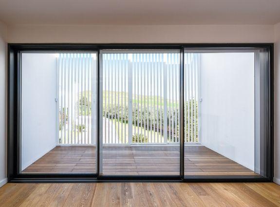 three pane slim sliding door with minimal aluminium framing and flush thresholds