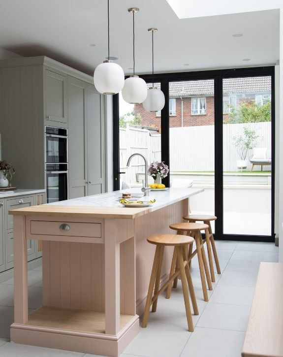 double height modern home extension with a pastel kitchen and contrasting black bifold door frames