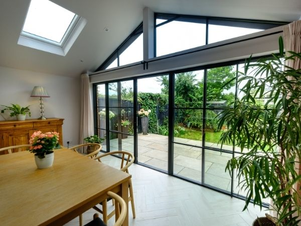 biparting sliding glass patio door with glazing bars and gable end window used to allow in a vast amount of natural light to this home
