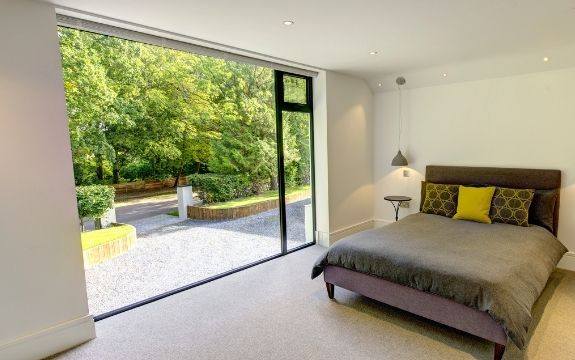 floor to ceiling fixed window with a top hung casement window used to create a glass wall that lets natural light into this bedroom