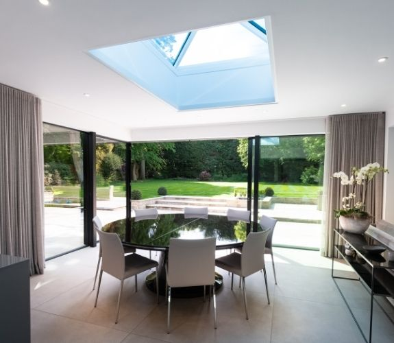 roof lantern and corner opening slim sliding doors maximising natural light in this contemporary dining room