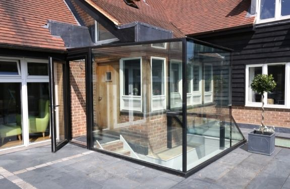 small glass box extension created using Invisio structural glazing and an aluminium casement door