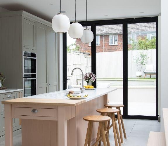 three pane aluminium bifold patio door that allow natural light into this modern kitchen extension