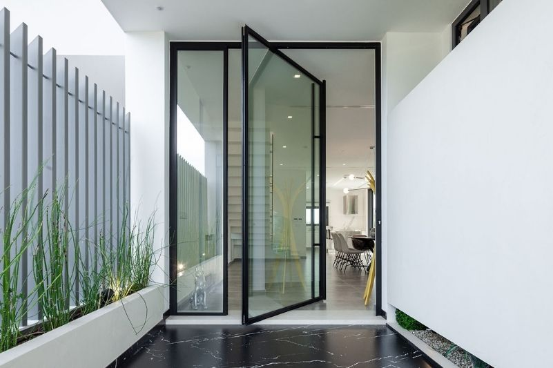 Sieger Lux Pivot Door with slim aluminium framing, a large pull handle and a fixed sidelight
